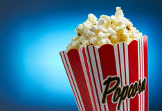Entertainment background with copy space. Popcorn over blue background, movie concept stock images