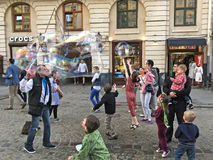 Entertainment for children - soap bubbles in the center of Lviv. LVIV, UKRAINE - MAY 06: Entertainment for children - A man blows bubbles for children in the stock photo