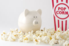 Entertainment Expenses. This is a white piggy bank and popcorn container and paper money. The concept is Entertainment expenses save money on entertainment Royalty Free Stock Photos