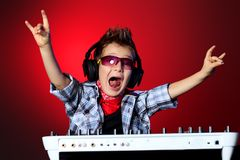 Entertainment. Expressive little boy DJ in headphones mixing up some party music Stock Image