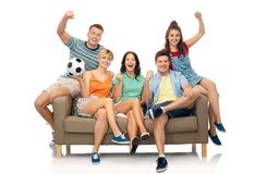 Friends or football fans with soccer ball on sofa Royalty Free Stock Photo
