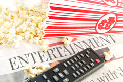 Entertainment news. Entertainment section of the newspaper with television remote controls and popcorn Royalty Free Stock Photography