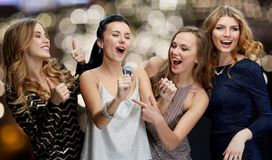 Women with microphone singing karaoke at christmas. Entertainment and people concept - happy women with microphone singing karaoke at new year party over Royalty Free Stock Image