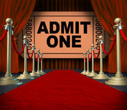 Entertainment On The Red Carpet. Theatrical cinema concept with an admit one movie ticket behind red velvet curtains and drapes as a symbol of an important Stock Photography