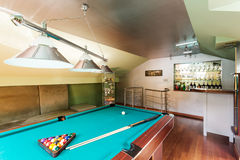 Entertainment room in an attic of a luxurious house. Close-up of a snooker table in an attic room with a home drink bar stock photography
