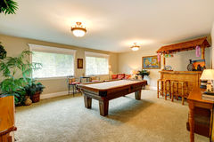 Entertainment room in hawaian style with pool table. Crafted wooden bar with rustic stools and palm trees Stock Photos