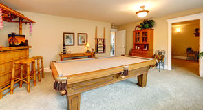 Entertainment room in hawaian style with pool table. Crafted wooden bar with rustic stools and palm trees Stock Images