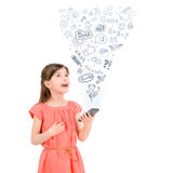 Entertainment with smartphone. Happy cute little girl in red dress holding a smartphone  in hand and fascinated looking up at the icons of different Royalty Free Stock Photo