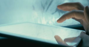 Entertainment with touch pad during travel. Close-up shot of a womans hand typing email or chat message on tablet computer while traveling by car stock footage