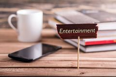 Entertainment sign. Entertainment on wooden sign with book , coffee cup and mobile phone on wooden table Royalty Free Stock Photos