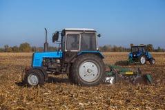 Entfernen der große blaue Traktor zwei, der ein Feld pflügt und die Überreste des vorher gemähten Mais Stockbild