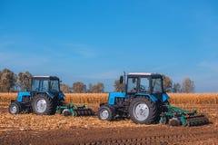 Entfernen der große blaue Traktor zwei, der ein Feld pflügt und die Überreste des vorher gemähten Mais Stockbilder