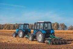 Entfernen der große blaue Traktor zwei, der ein Feld pflügt und die Überreste des vorher gemähten Mais Lizenzfreie Stockfotos