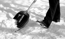 Entfernen des Schnees mit einer Schaufel nach Schneefällen Stockfotos