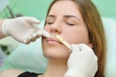 Entfernen des Schnurrbartes einer Frau mit heißem Wachs in einem Schönheitssalon Lizenzfreies Stockbild