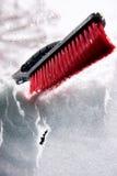 Entfernen Sie Schnee mit Bürste von der Autowindschutzscheibe am Wintertag Lizenzfreie Stockfotografie
