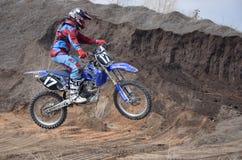 Entfernt sich auf einem hohen Damm von Erde auf Motorrad Stockfotografie