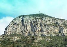 Entfernte Ansicht eines Kreuzes auf einem Berg mit bloßem Klippen ouside Sorrent, Italien Stockfoto