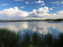 Entfernter Regen und Wolken reflektiert im Minnesota See Stockfotos