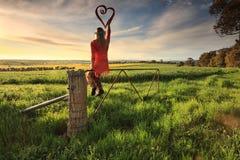 Entgehen Sie zum Land - Frau auf Zaun mit Liebesherzen im morni stockbild