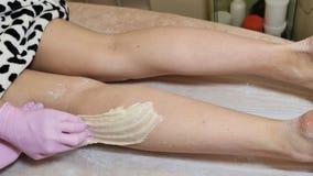 Enthaarung von Beinen mit Zuckerpaste oder Shugaring Schönheits-Saal lizenzfreie stockfotografie