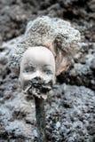 Enthauptete Mädchenpuppe mit furchtsamem geschmolzenem Gesicht Stockfotografie
