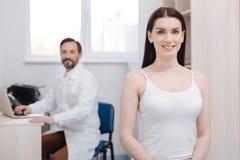 Enthousiaste bevallige vrouw die plastic chirurg voor het opheffen van procedure bezoeken stock fotografie