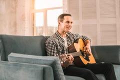 Enthousiaste creatieve mens die zijn gitaar speelvaardigheden beheersen royalty-vrije stock afbeelding
