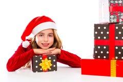 Enthousiaste heureux de fille d'enfant de Santa de Noël avec des cadeaux de ruban Image libre de droits