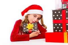 Enthousiaste heureux de fille d'enfant de Santa de Noël avec des cadeaux de ruban Images stock
