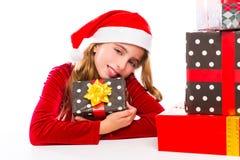 Enthousiaste heureux de fille d'enfant de Santa de Noël avec des cadeaux de ruban Images libres de droits