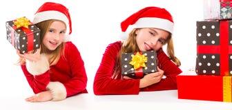 Enthousiaste heureux de filles de soeur d'enfant de Santa de Noël avec des cadeaux de ruban Image libre de droits