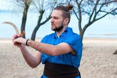 Enthousiaste mens in blauwe kimono, broodje en stokken bij de hoofd opleiding met zwaard royalty-vrije stock fotografie