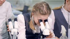 Enthousiaste schoolmeisjes die wetenschapsexperiment in schoollaboratorium doen stock video