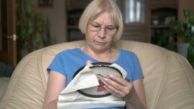 Enthralled koncentrerade snyggt högt kvinnasammanträde i arg sy bild för stol hemma stock video