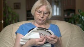 Enthralled koncentrerade snyggt högt kvinnasammanträde på arg sy bild för stol hemma lager videofilmer
