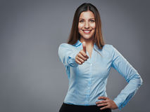 Enthusiastic approval. Confident young businesswoman giving the thumbs up against a gray background royalty free stock photography