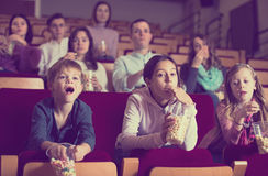 Enthusiastic audience attending movie night with popcorn Stock Image