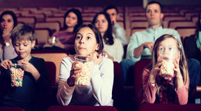 Enthusiastic audience eating popcorn and watching a movie Stock Photos