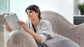 Enthusiastic beautiful woman enjoying reading interesting book alone at cozy home interior. Medium close-up. Cosiness charming winter female wearing woolen stock video footage