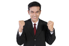 Enthusiastic businessman with clenched fists, isolated on white. Overly enthusiastic expression of young Asian businessman looking straight to camera with teeth Royalty Free Stock Photography