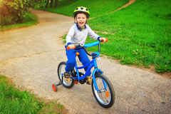 An enthusiastic cheerful child on a bicycle in green park is happy and screams with excitement of fun. A boy riding a bike in nature along path in park in Stock Photography