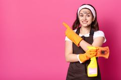 Enthusiastic cheerful woman standing isolated over pink background in studio, holding detergent and dirty washcloth in one hand, stock photography