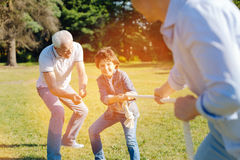 Enthusiastic committed fun men tugging the rope. Standing firm. Attractive emotional sweet kid spending the day with his family while the dad playing with him royalty free stock photography
