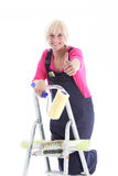 Enthusiastic decorator on a ladder. Enthusiastic female decorator on a ladder giving a thumbs up gesture of approval and success for her DIY wallpapering project Stock Photo