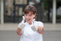 Enthusiastic doctor giving a thumbs up gesture. Enthusiastic attractive female nurse or doctor giving a thumbs up gesture with both gloved hands celebrating a Stock Photography