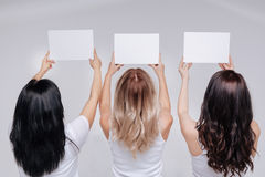 Enthusiastic female activists posing with white signs. Looking to the future. Gorgeous elegant powerful standing with their hands being up in the air holding royalty free stock photo