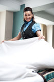 Enthusiastic female attendant arranging bed sheet. Loving her work Royalty Free Stock Image
