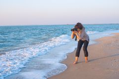 An enthusiastic female  photographer takes a picture. On the seashore during sunset Stock Photo