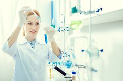Enthusiastic female scientist conducting chemical experiment. Future breakthrough. Waist up shot of an amazed adult researcher using a pipette while pouring royalty free stock photo